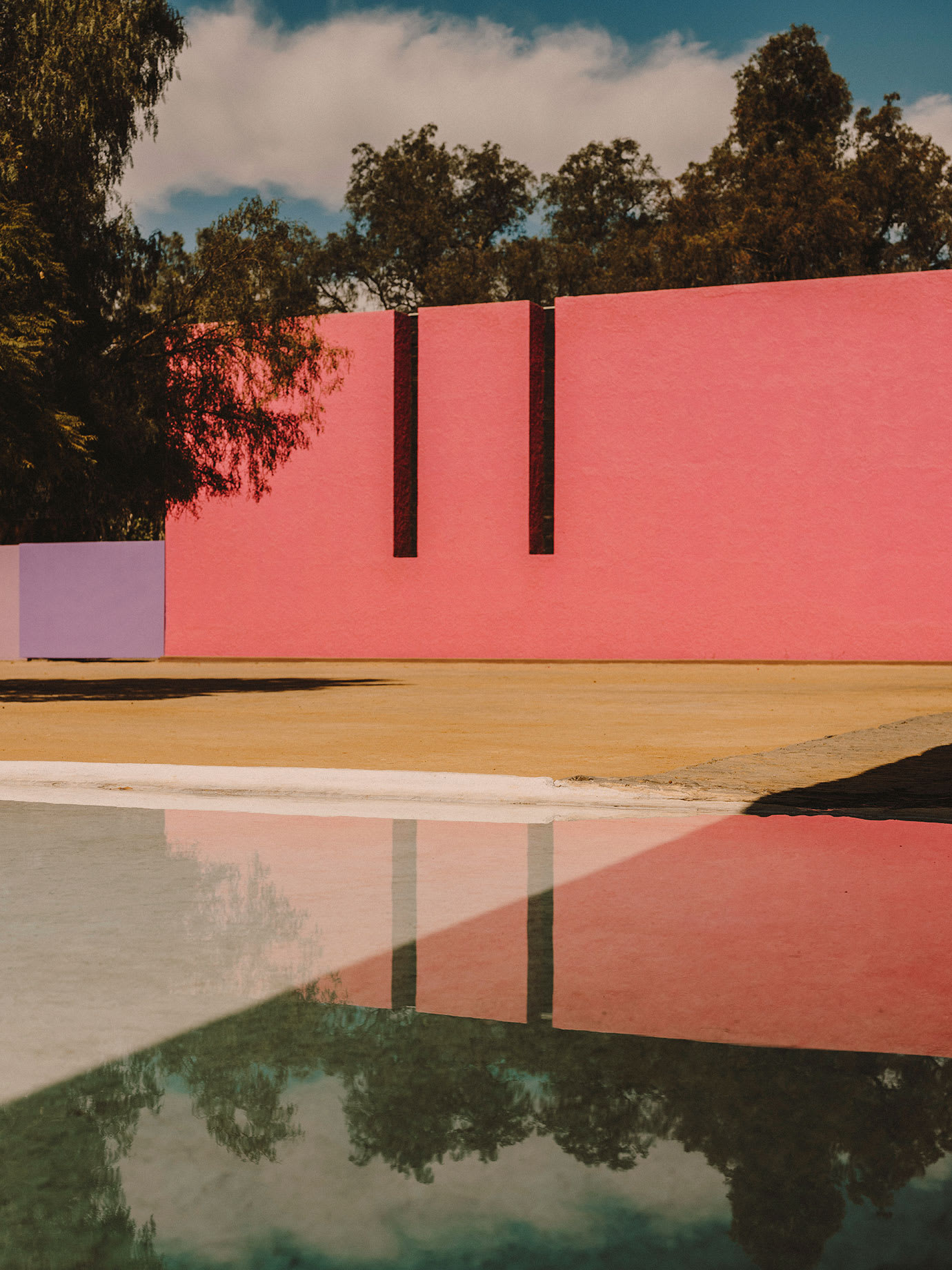 An outdoor area with a pink wall.