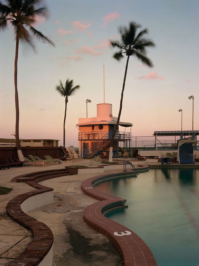 An outdoor swimming pool with palm trees at sunset.