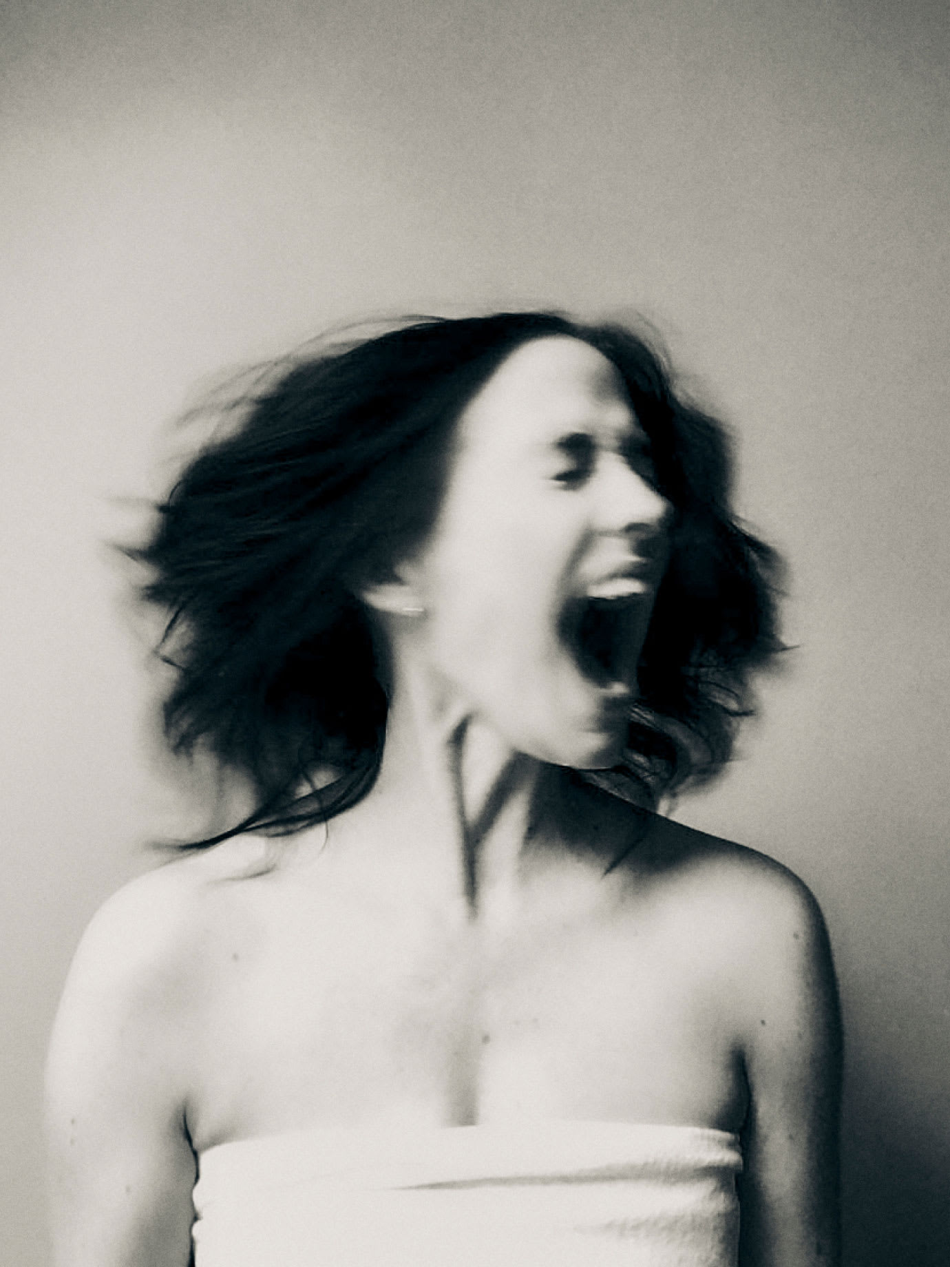 A woman screaming while shaking her head.