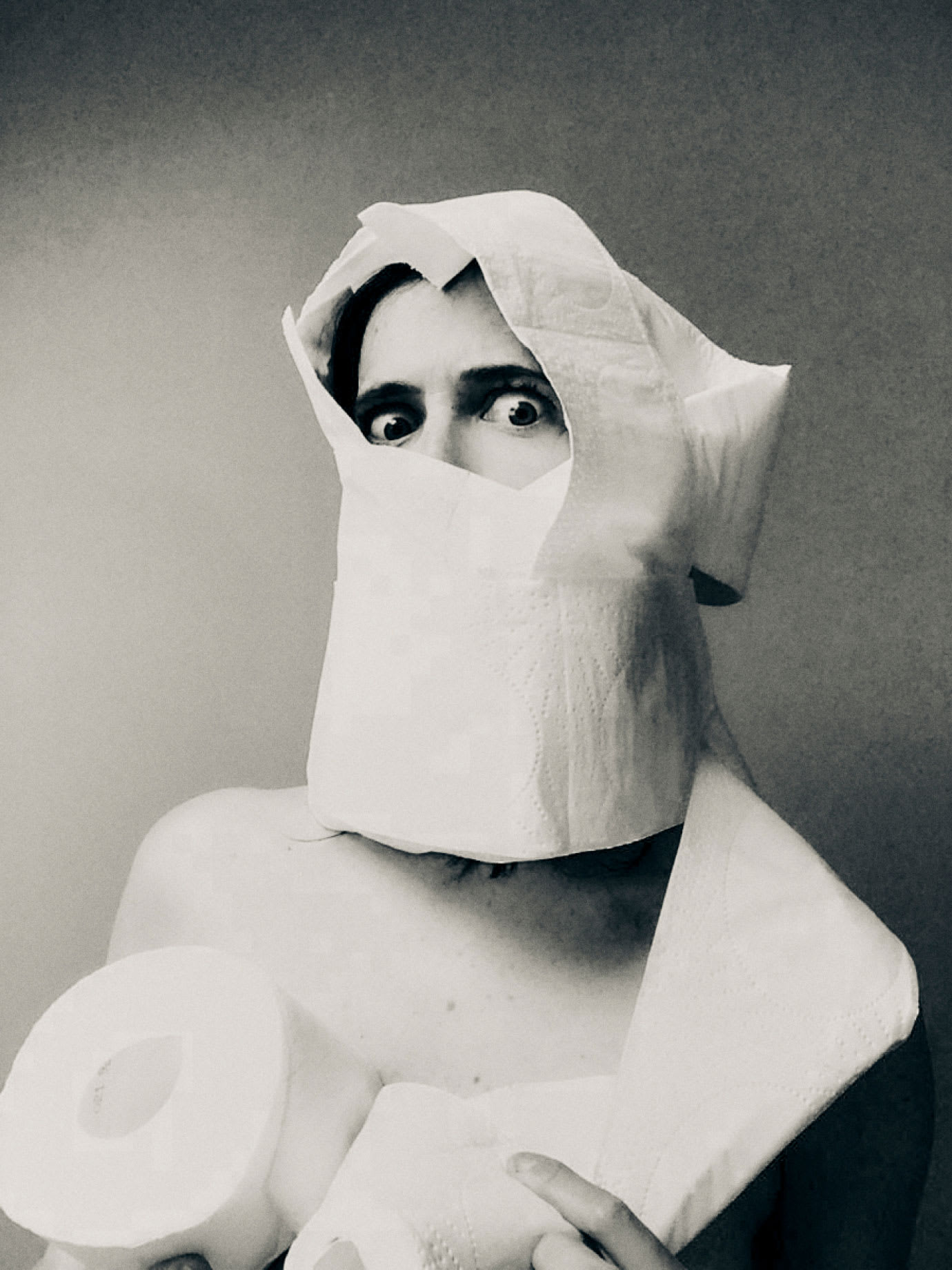 A woman covered in rolls of toilet paper.