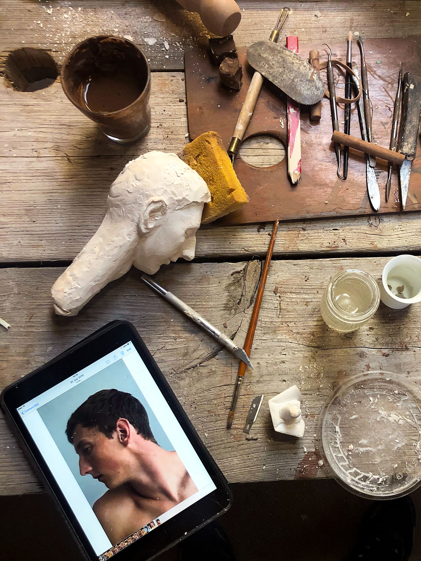 A workbench with sculptors tools and an iPad on it.
