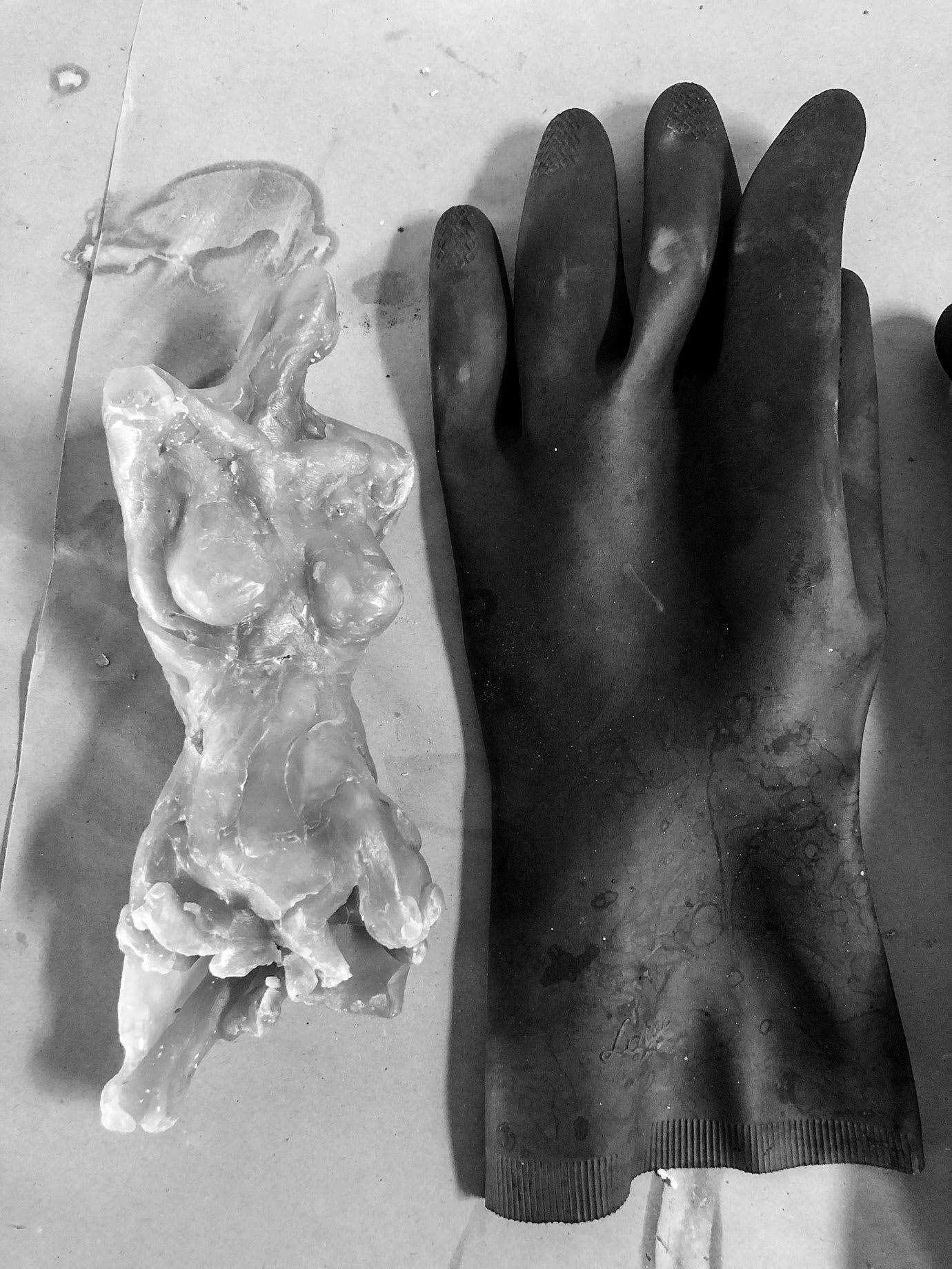 A wax model of a female body next to a black glove.