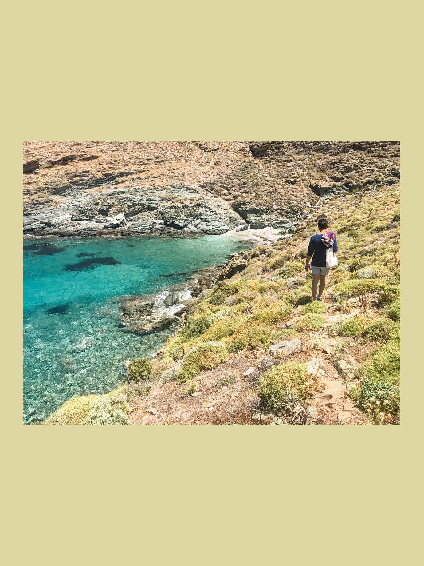 A man walking down a path towards the sea.