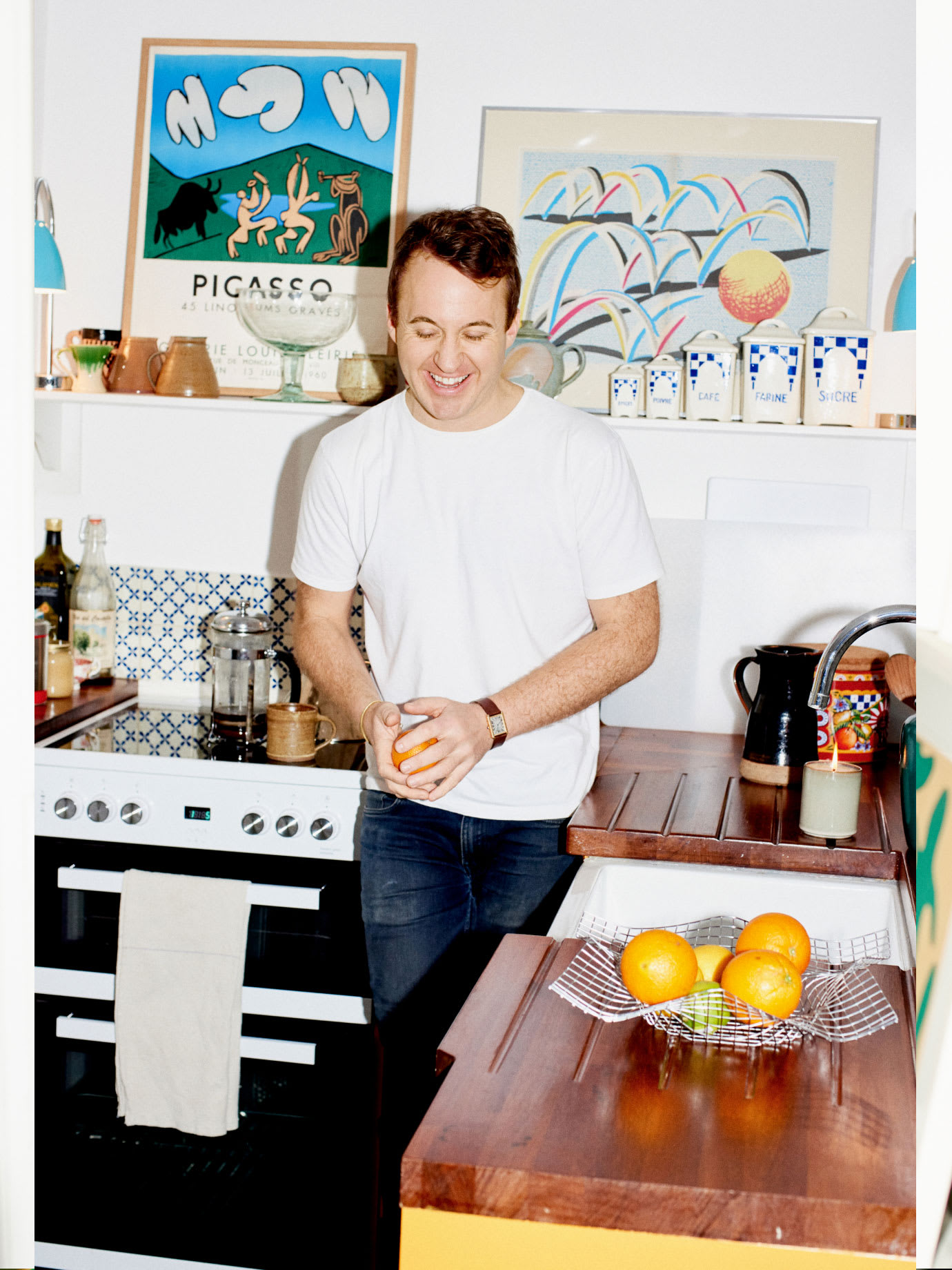 A man laughing in his kitchen.