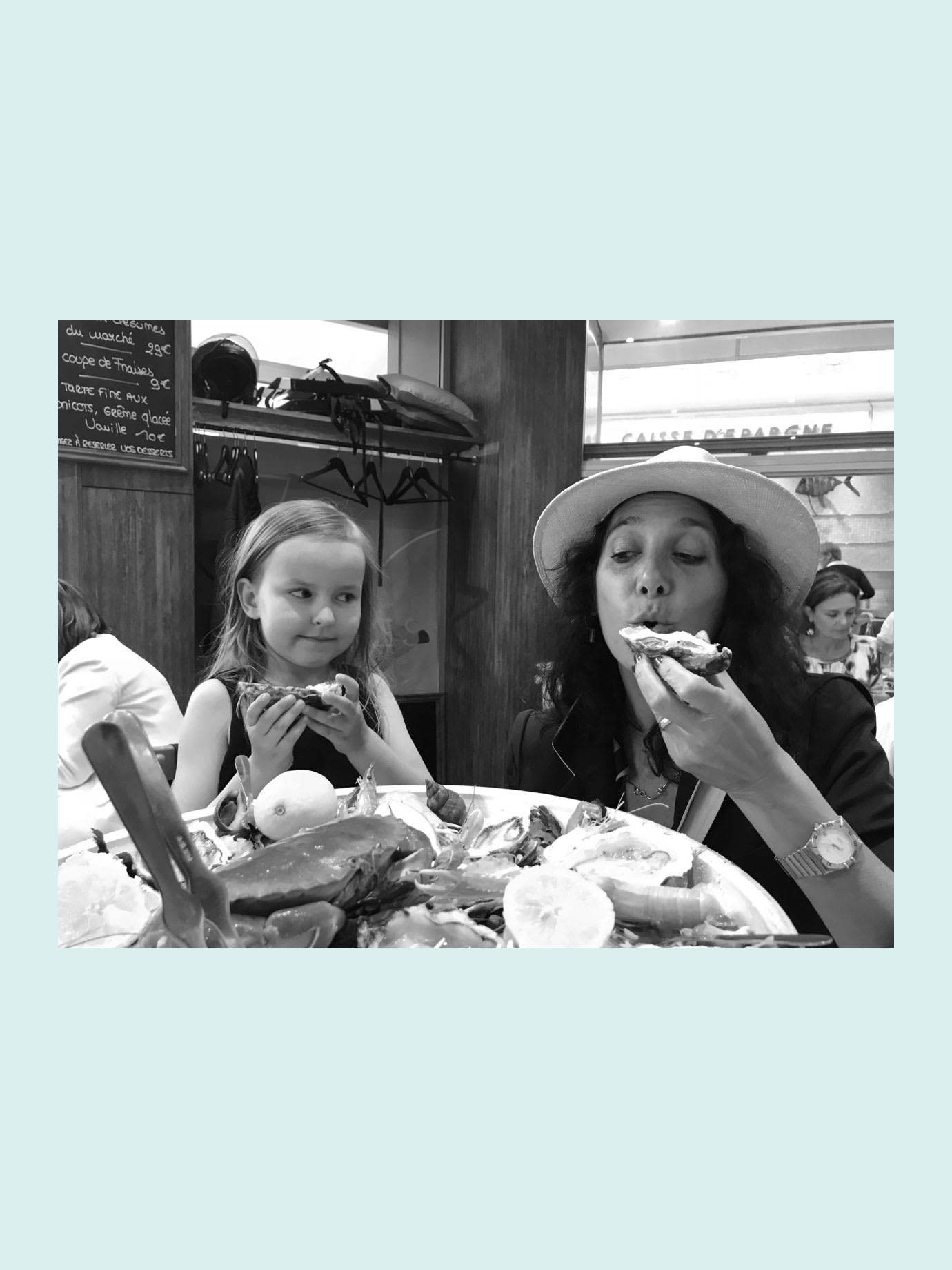 A woman and a young girl eating oysters in a restaurant.