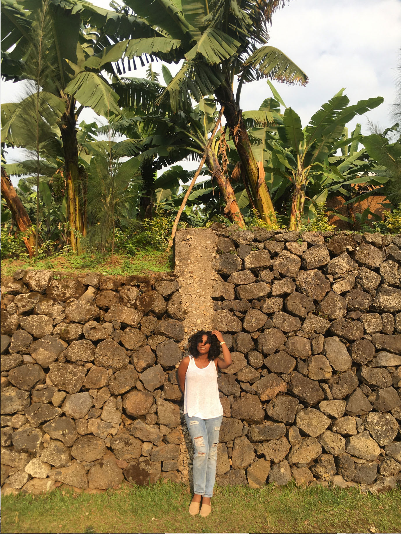 A woman standing in front of a stone wall.