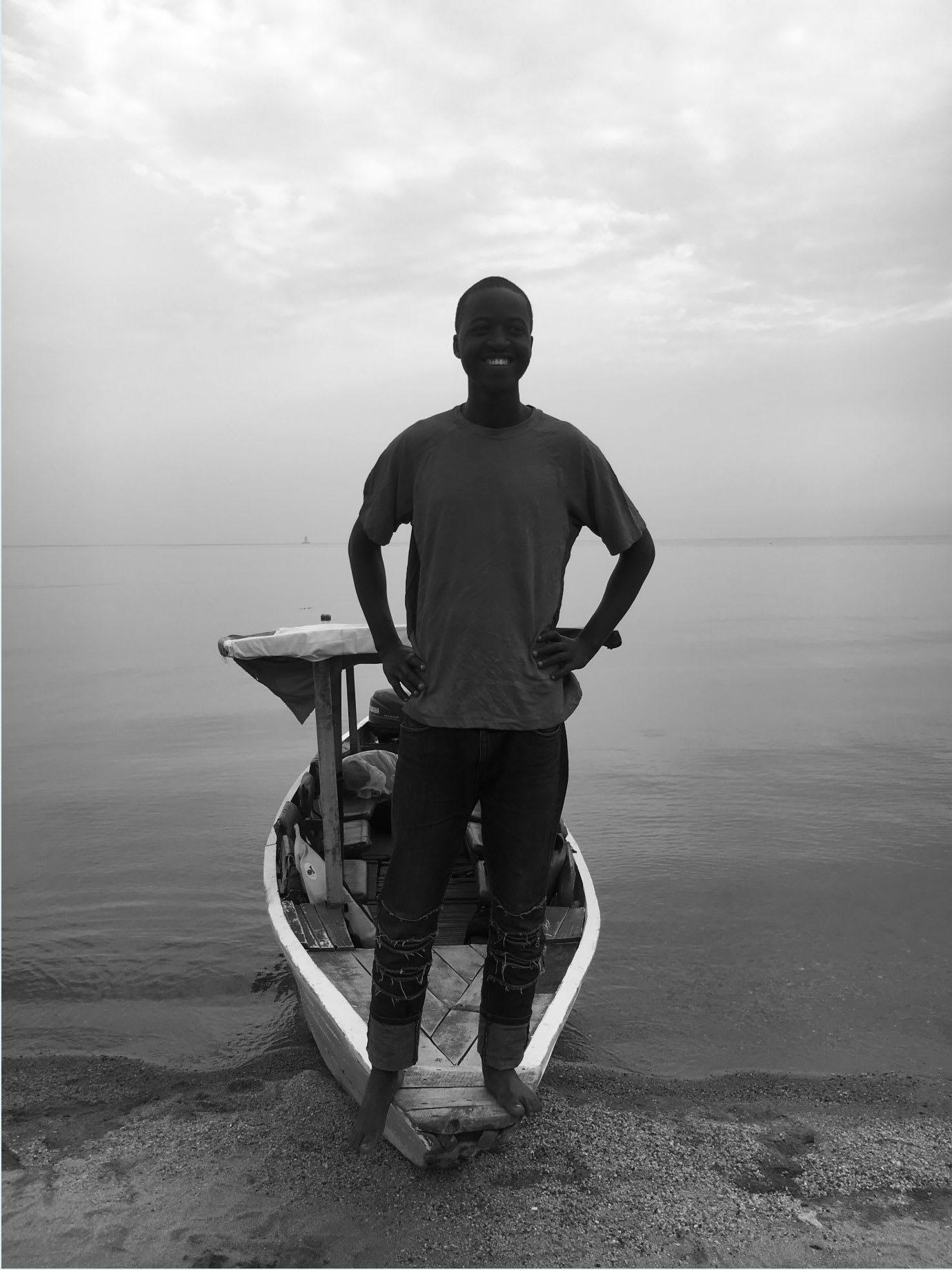 A man standing on a canoe on a beach.