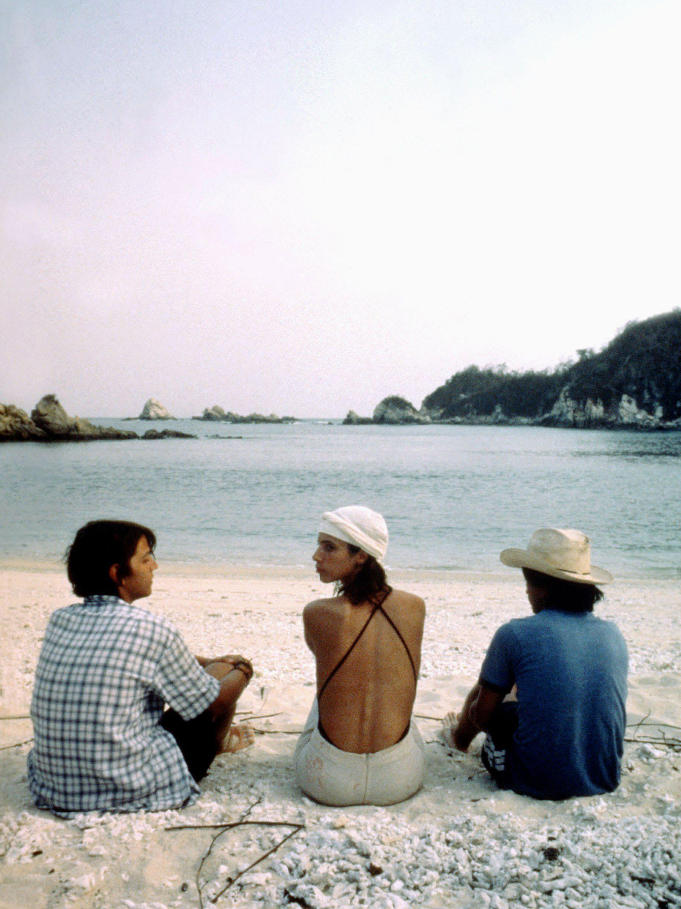 A woman and two men sitting on a beach and looking at the sea.