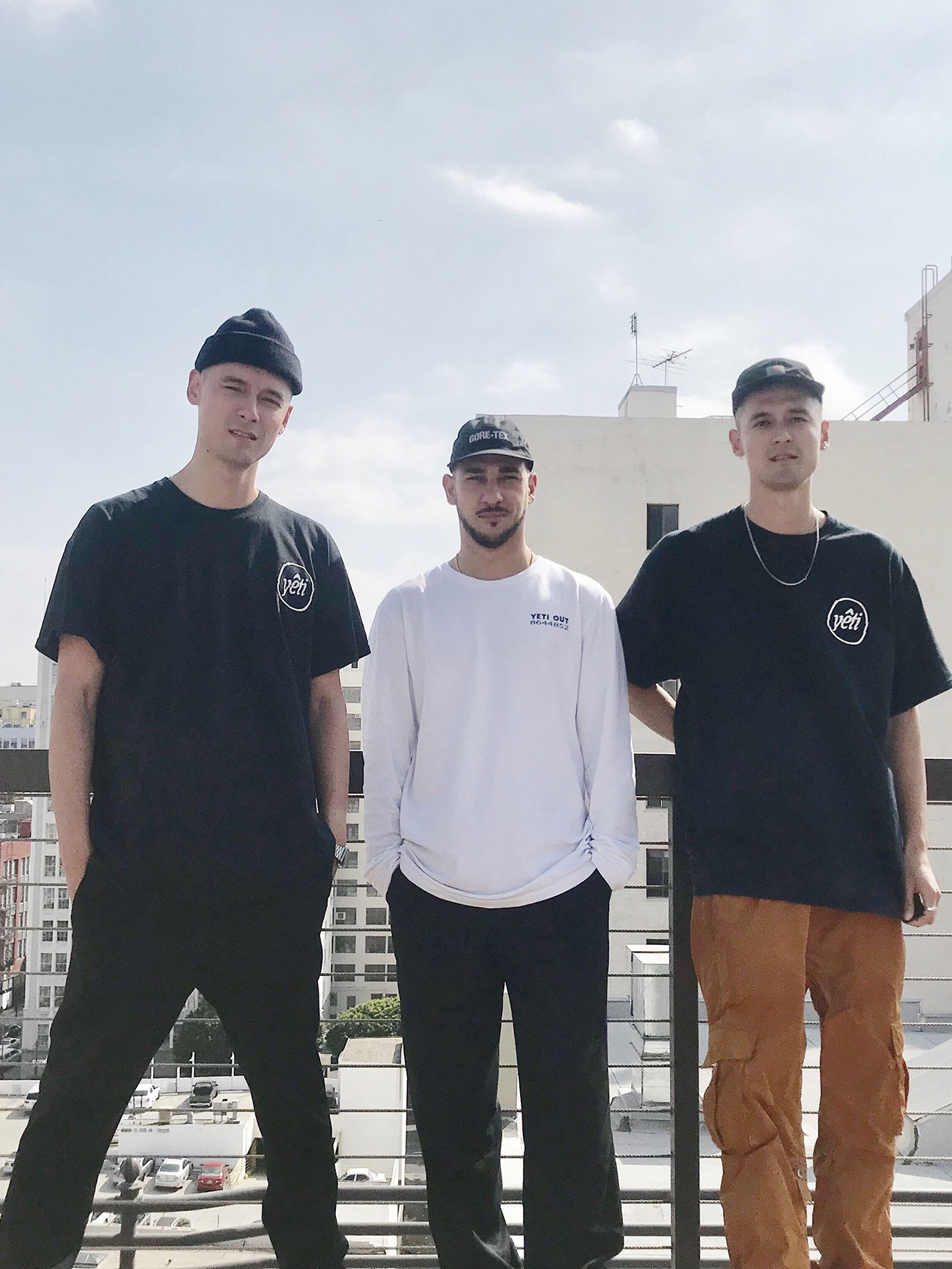 Three men standing on a roof in a city.