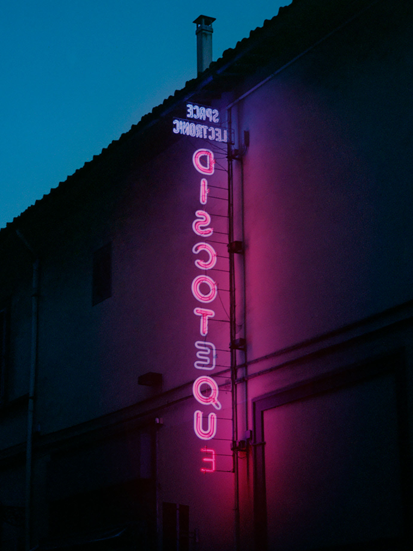 A purple neon sign on the side of a building.