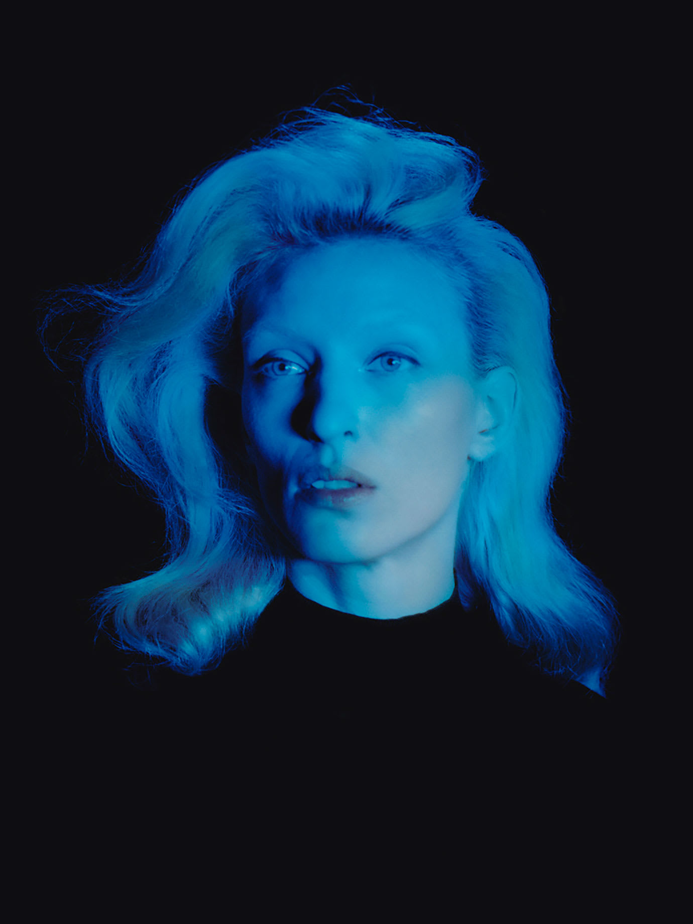 A blonde woman with a blue light on her.