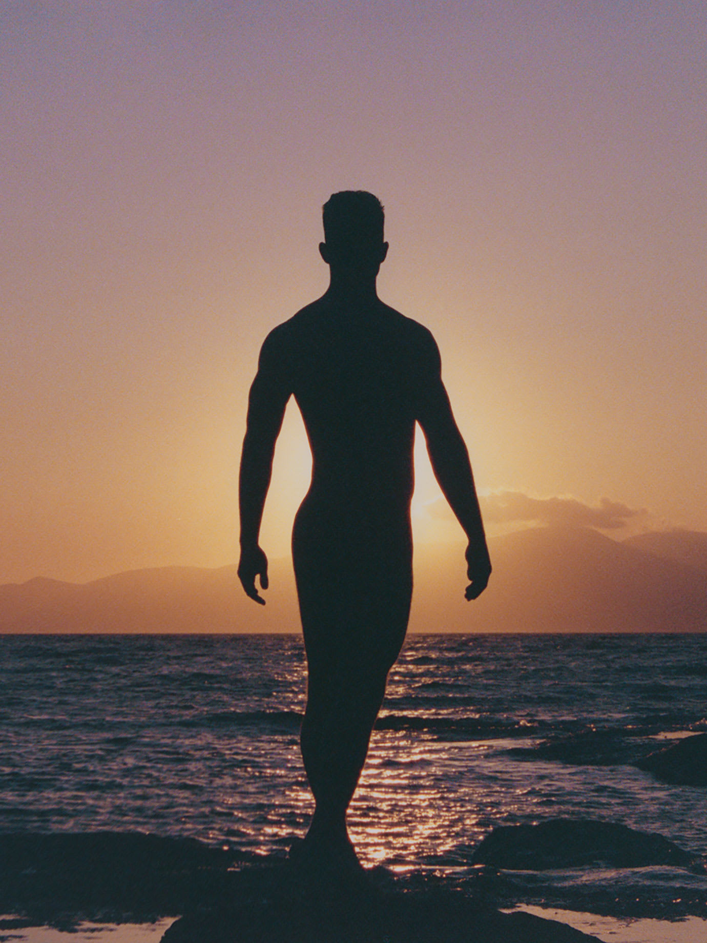 A man in silhouette by the sea.