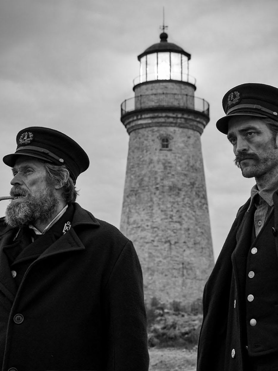 Two men standing outside a lighthouse.