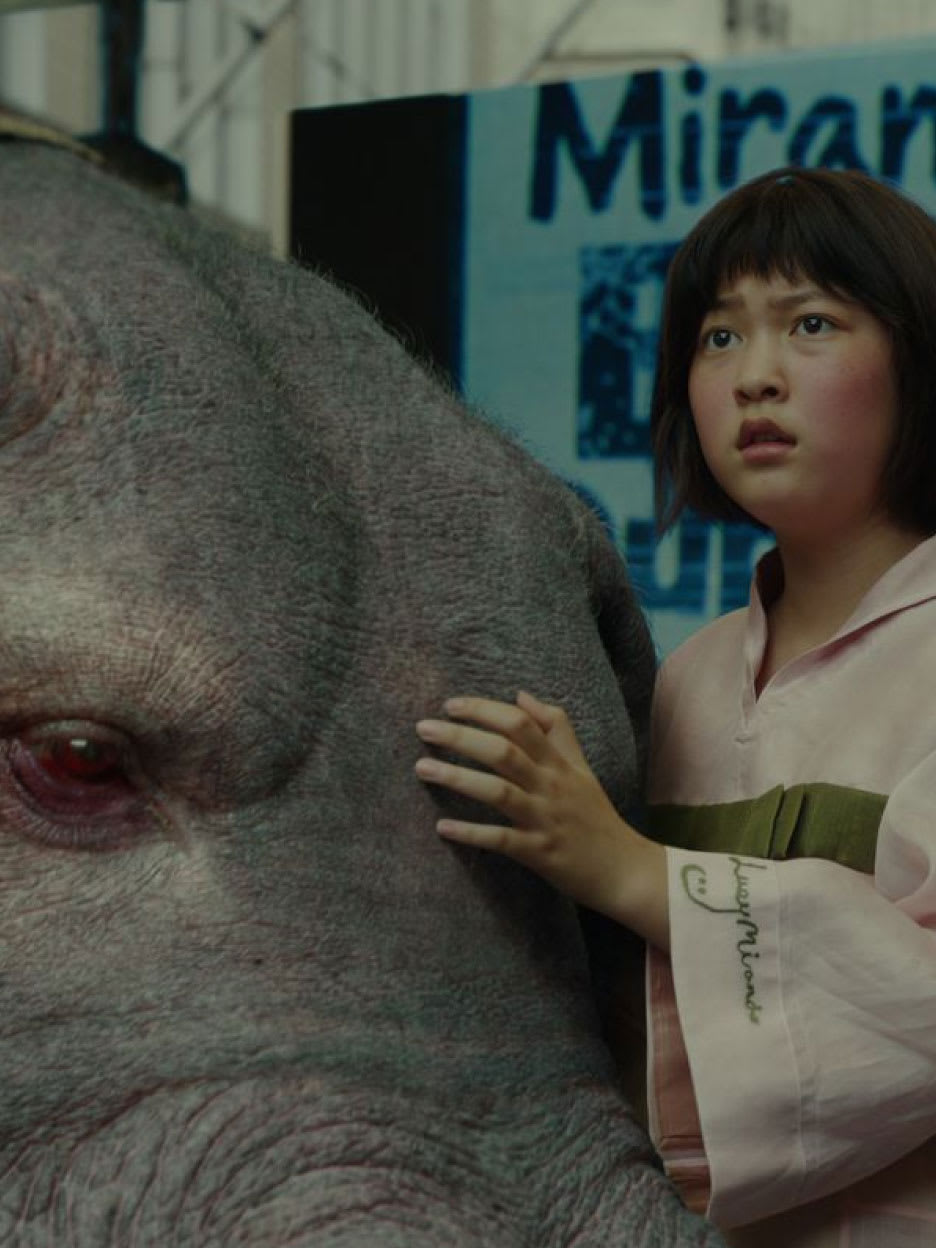 A young girl with her hand on a giant animal.