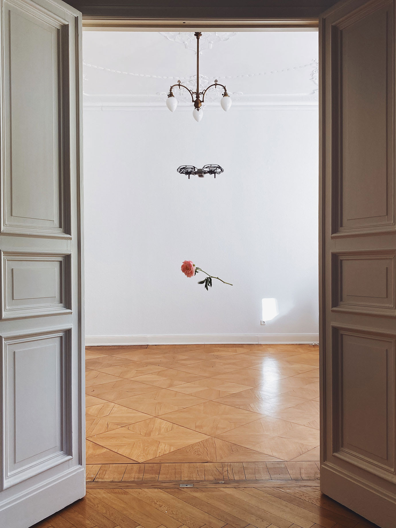 A flower hanging from a drone flying in a hallway.