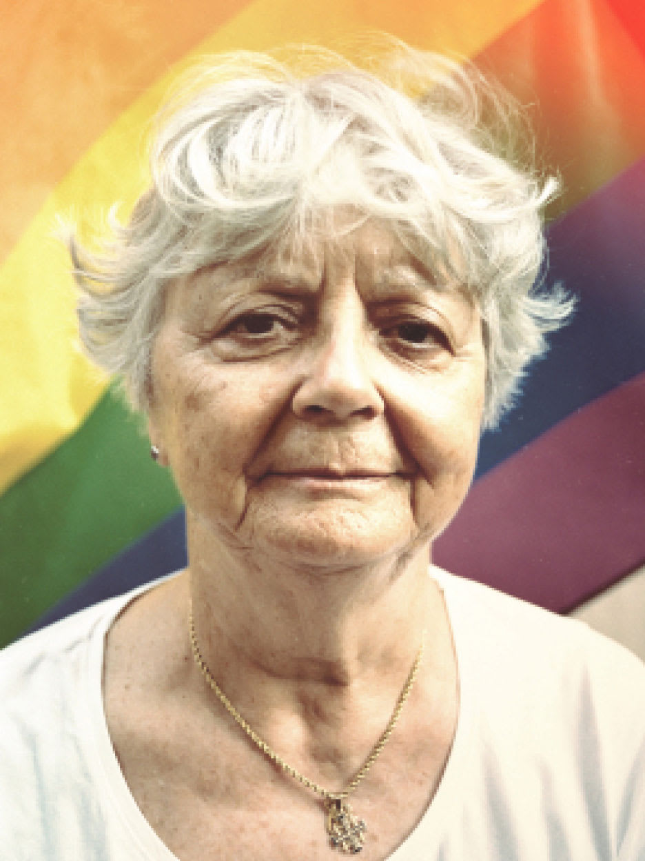 An elderly woman standing in front of a rainbow flag.