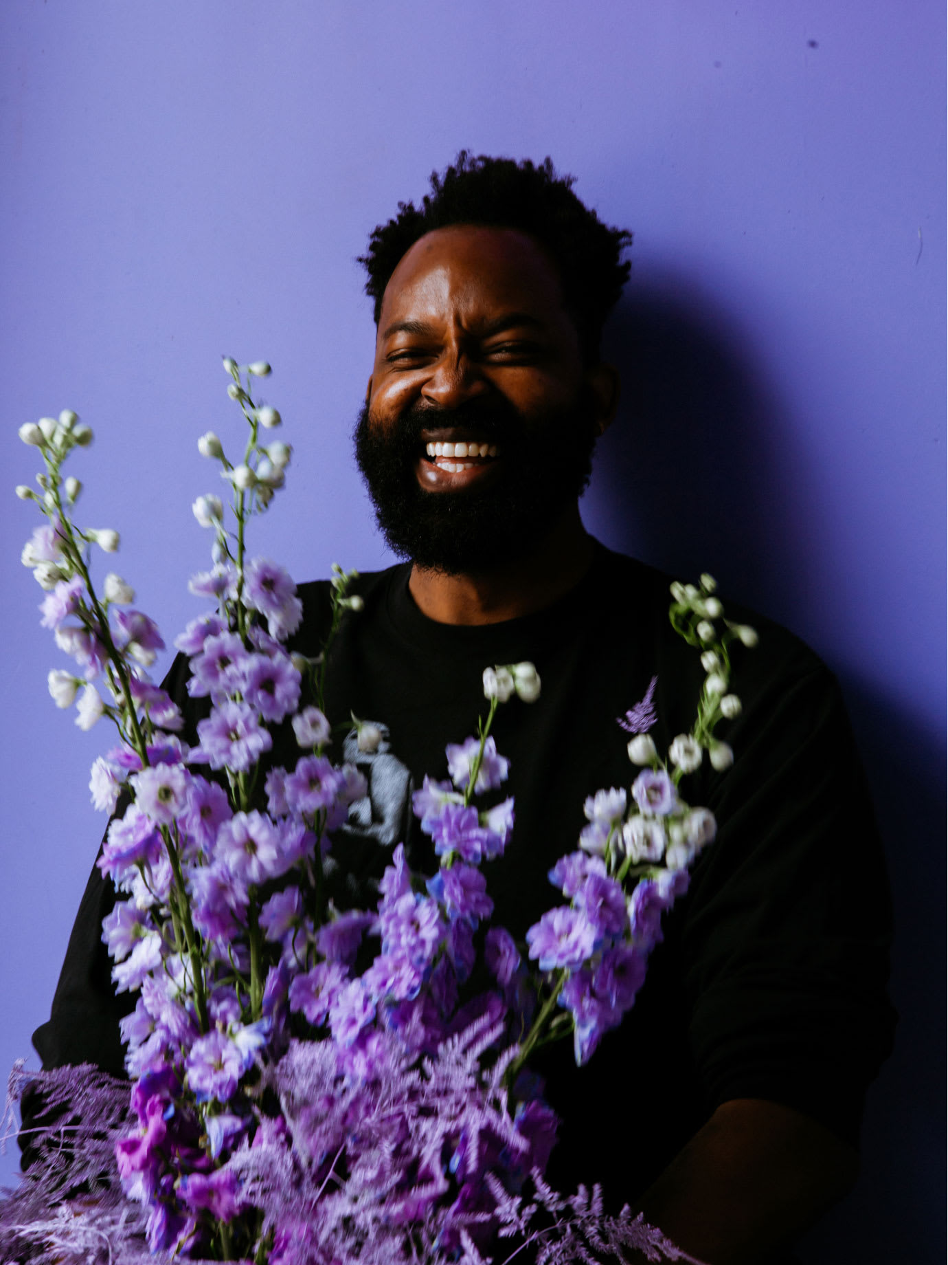 A laughing man holding purple flowers in front of a purple background.