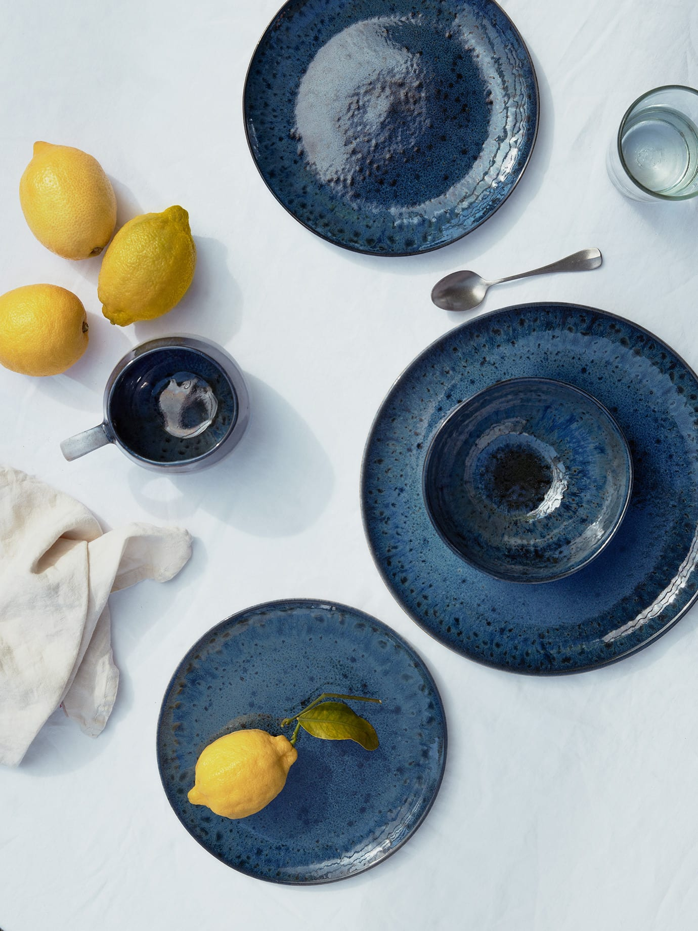Lemons and blue tableware on a table top.