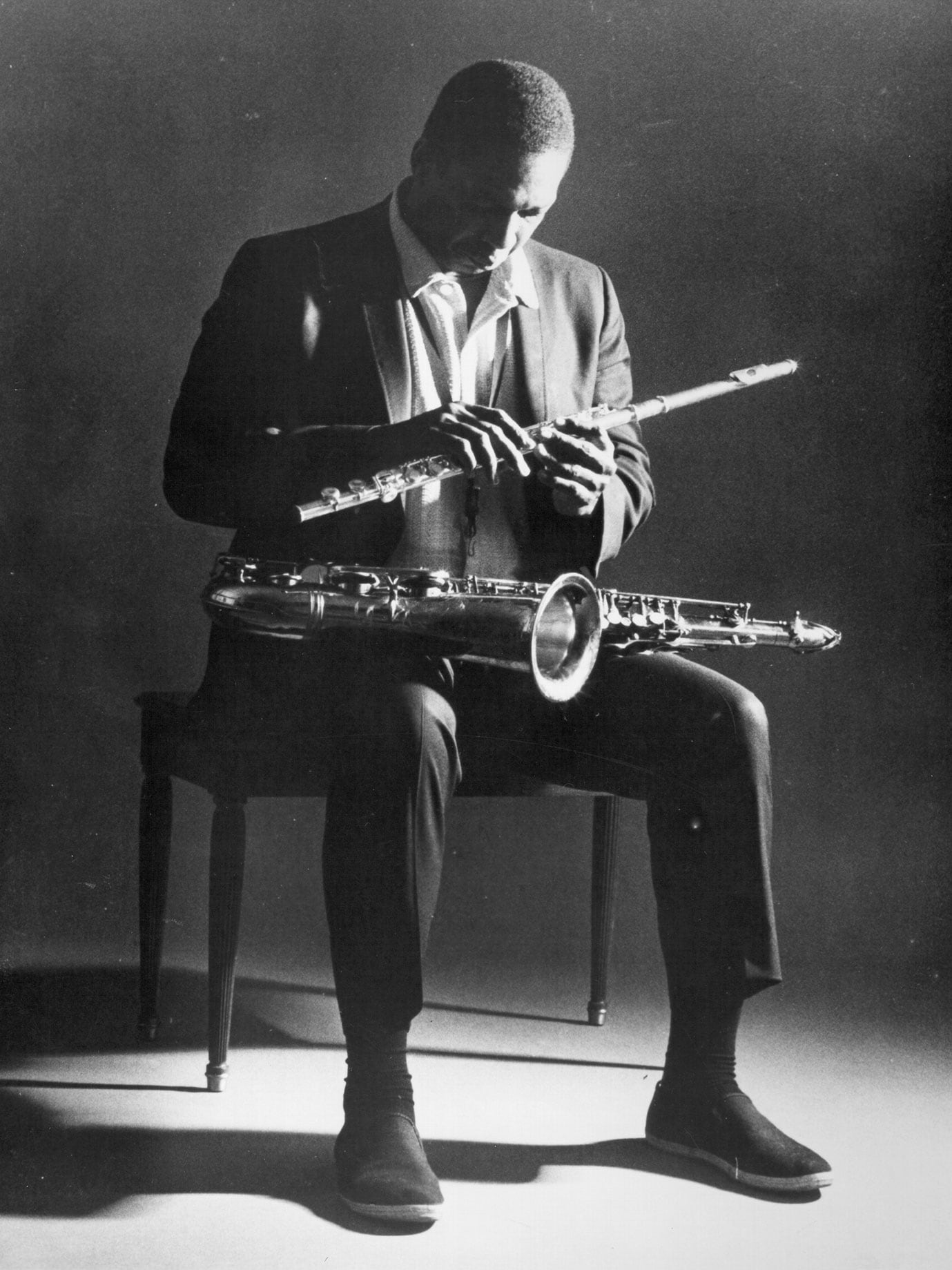 A man sitting on a chair holding a flute and a saxophone.