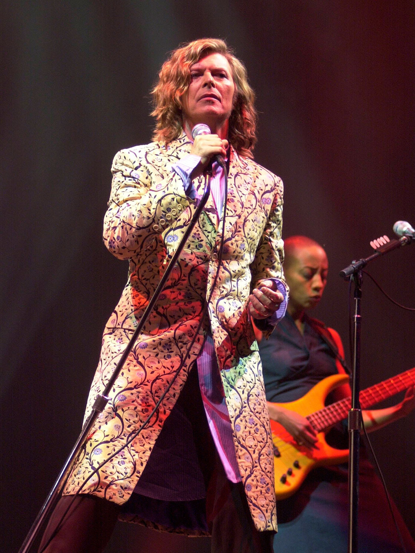 A man singing on a stage in a long coat with long hair.
