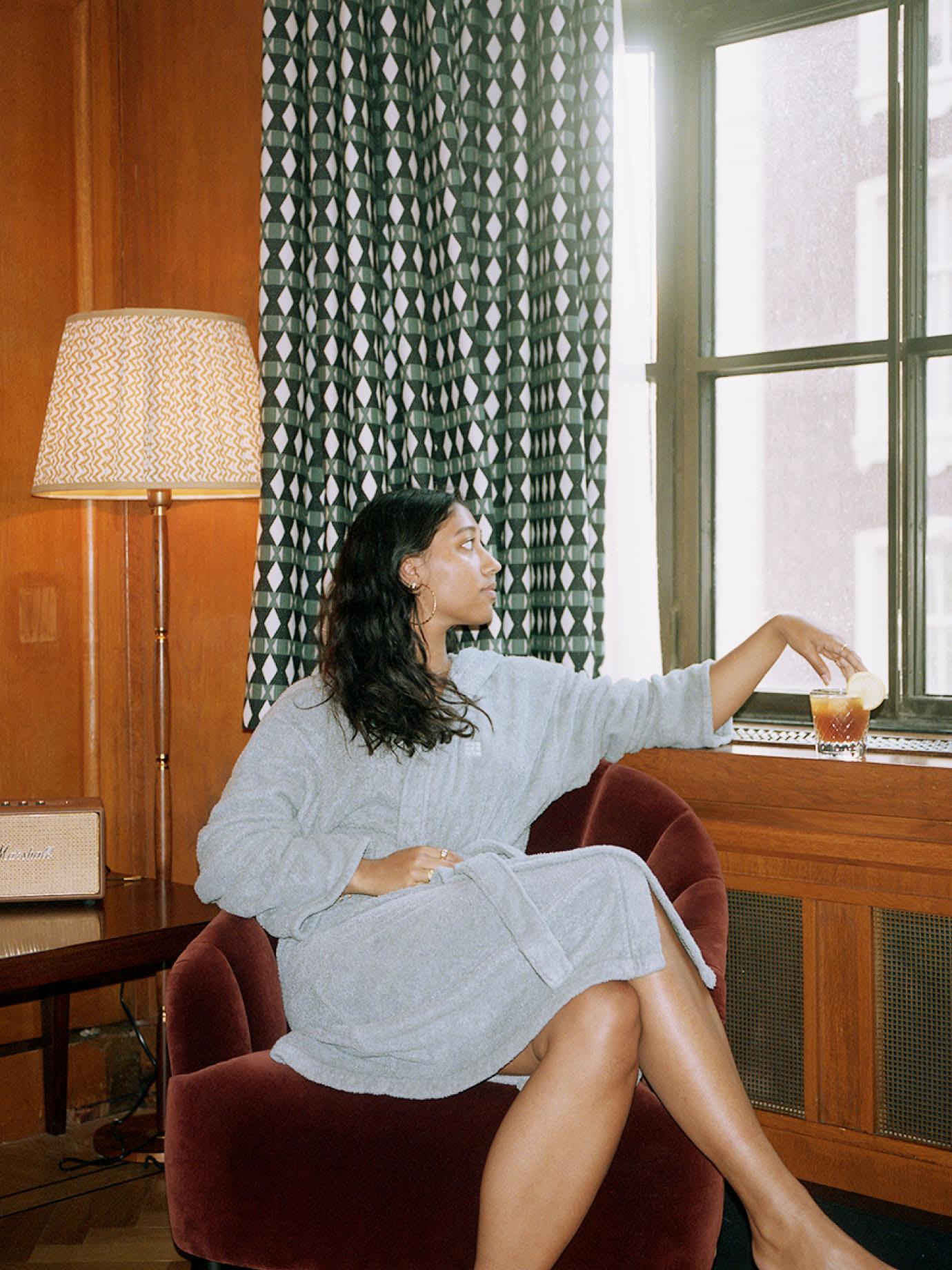 A woman sitting in a chair in a bathrobe.