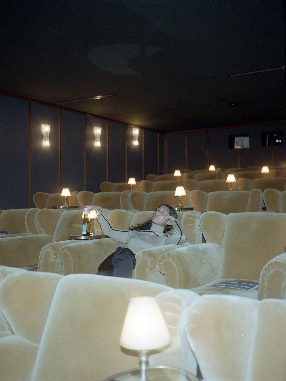 A woman sitting in a dark cinema.