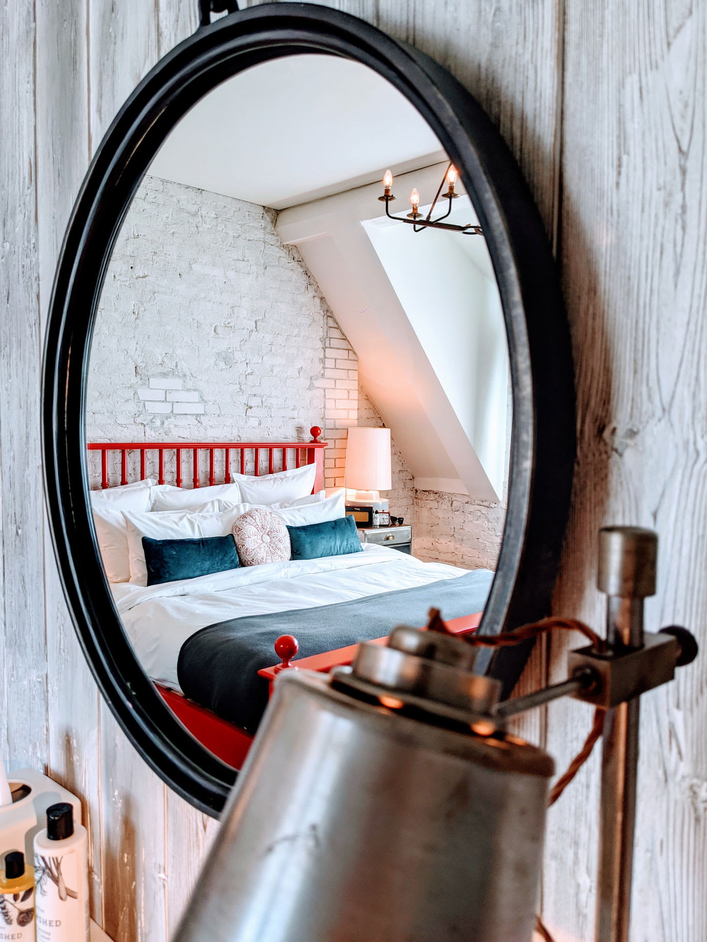 A bed reflected in a mirror.