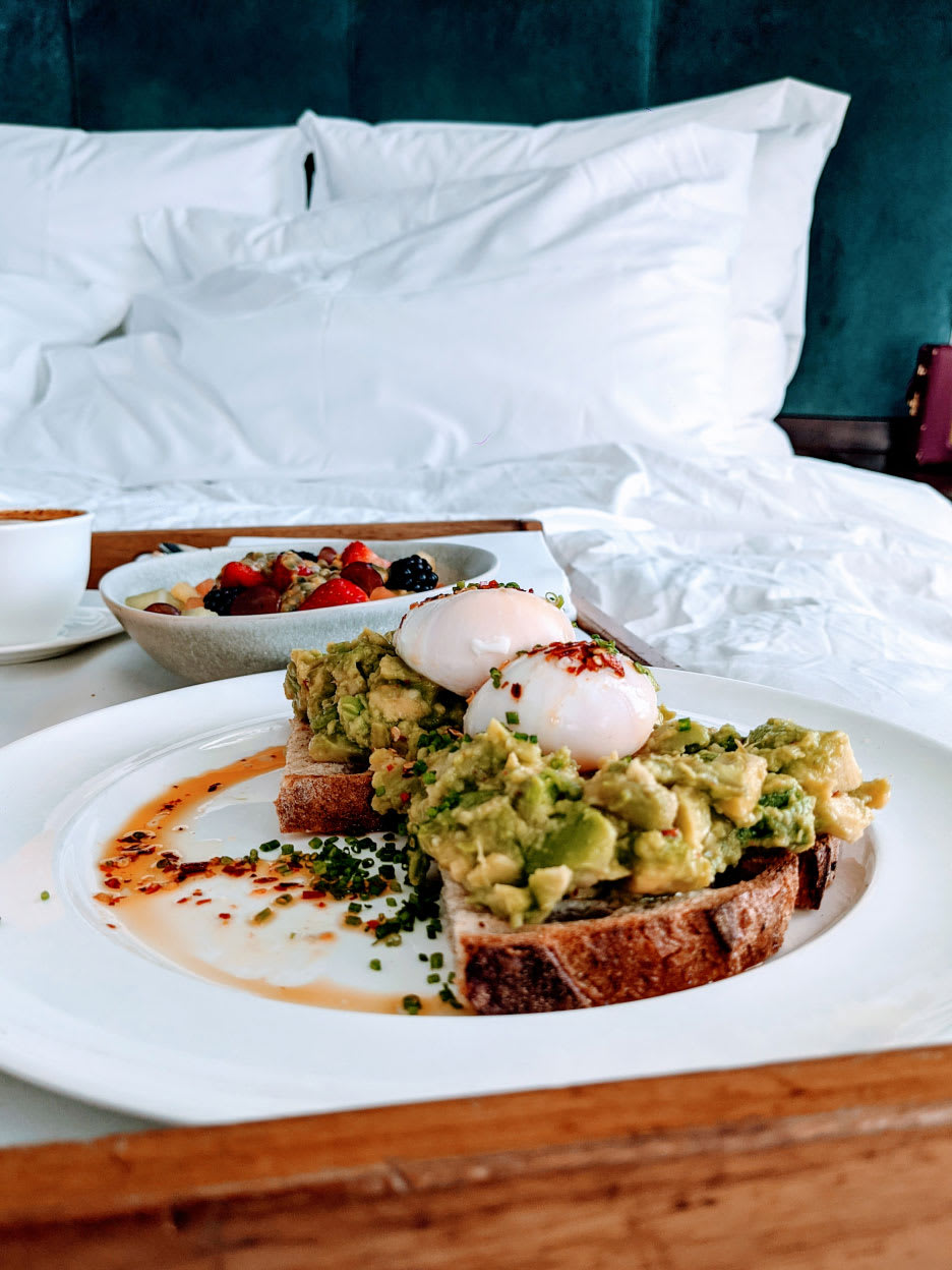 Room service on a tray on a bed.