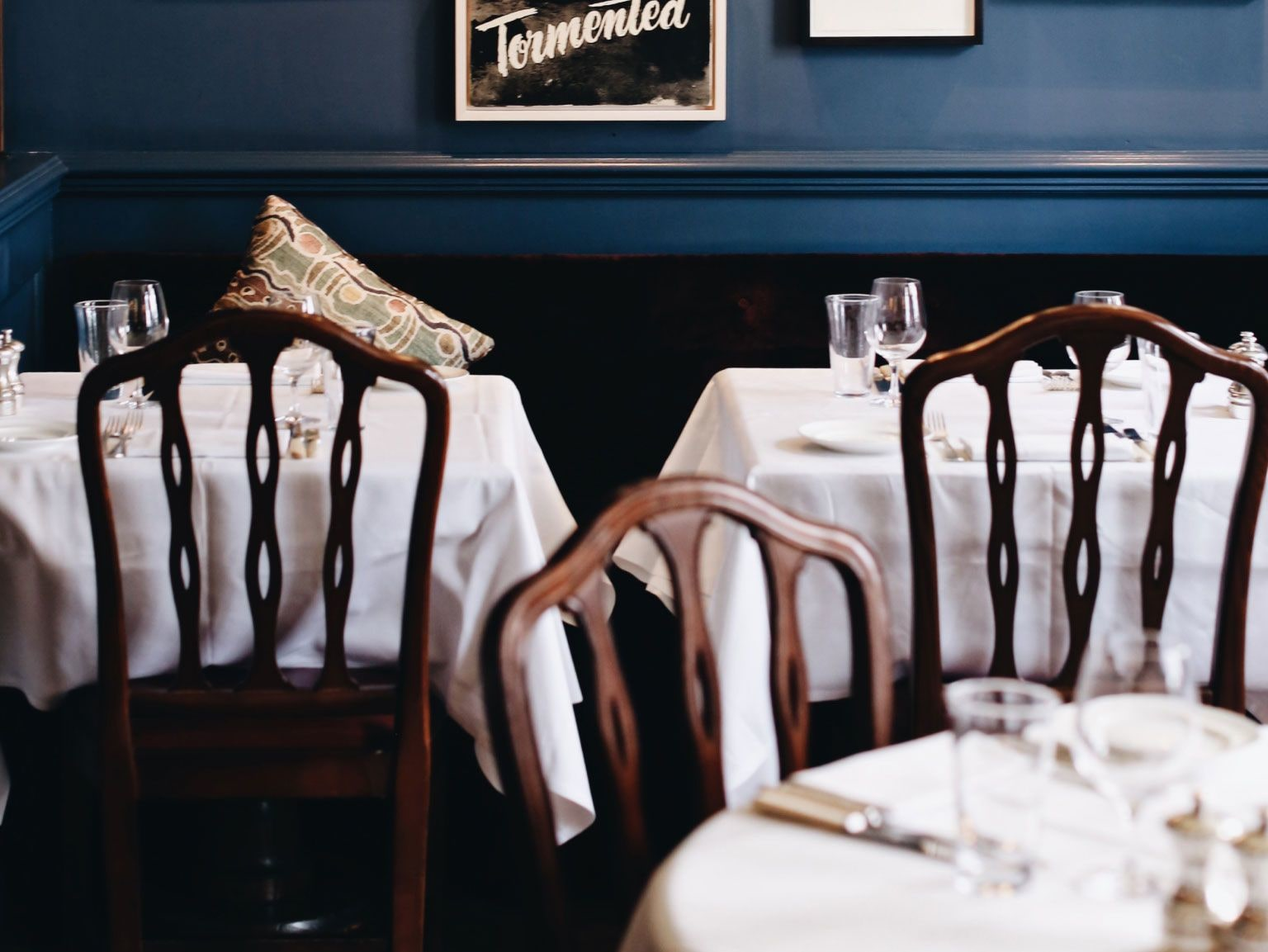 Three tables laid for dinner in a blue room.