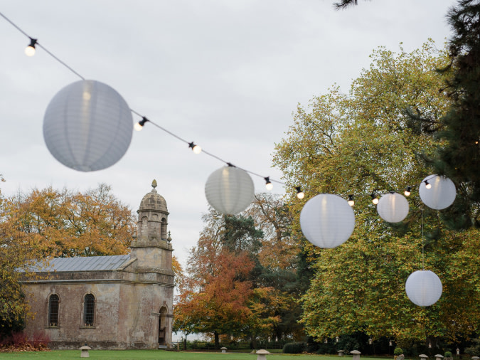 Paper lanterns strung up in the air with a chapel in the background.