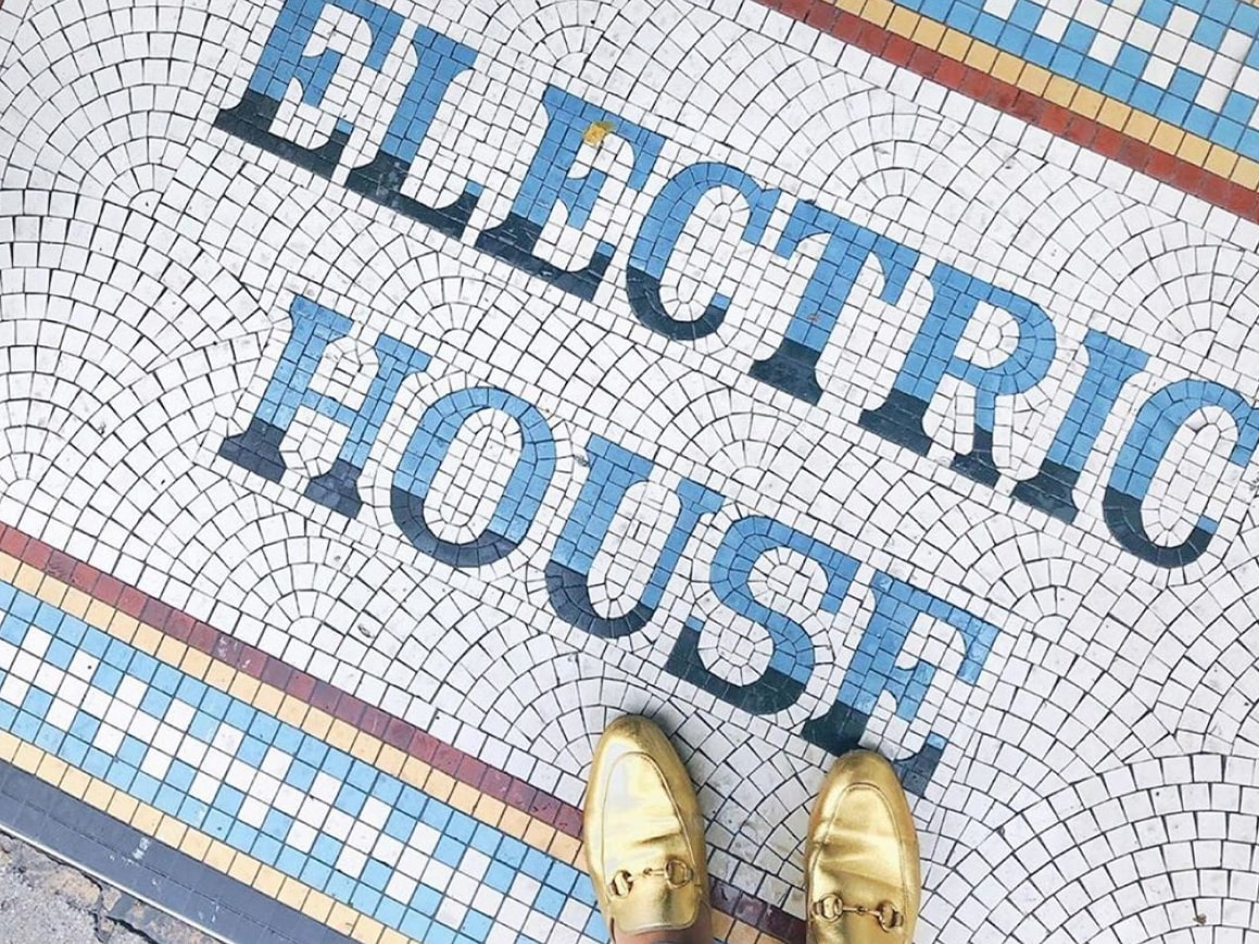 A person wearing gold shoes standing on a mosaic saying Electric House.