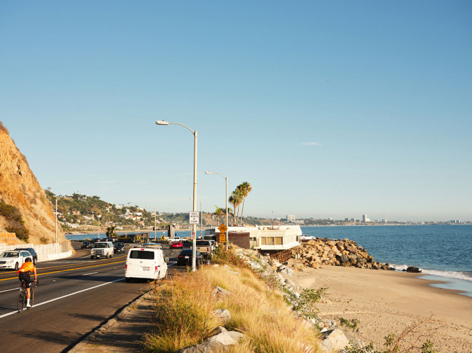 A coastal highway with cars next to the sea.