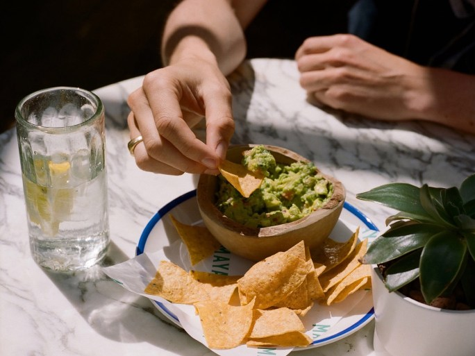 A person dips tortilla chips into a bowl of guacamole.
