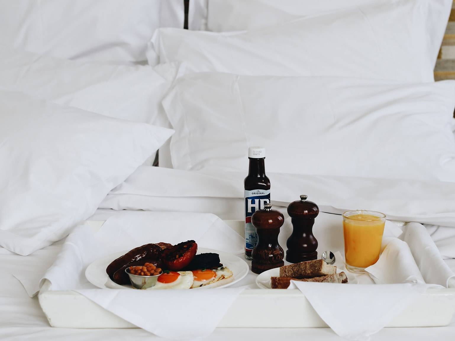 A bed with a room service tray with breakfast on it.