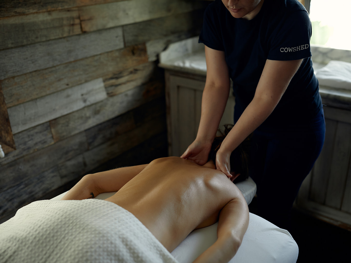 A person receiving a back massage in a spa.