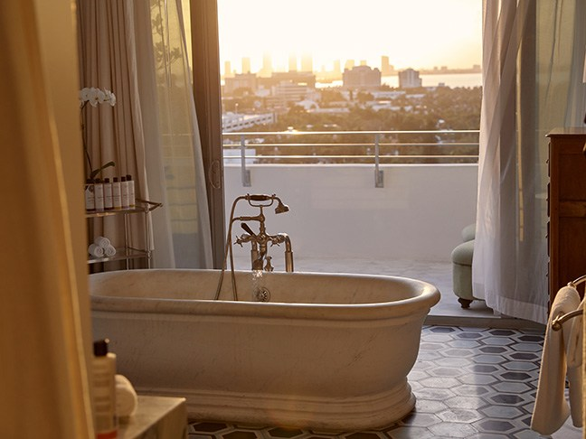 A roll top bath next to a balcony at sunset.