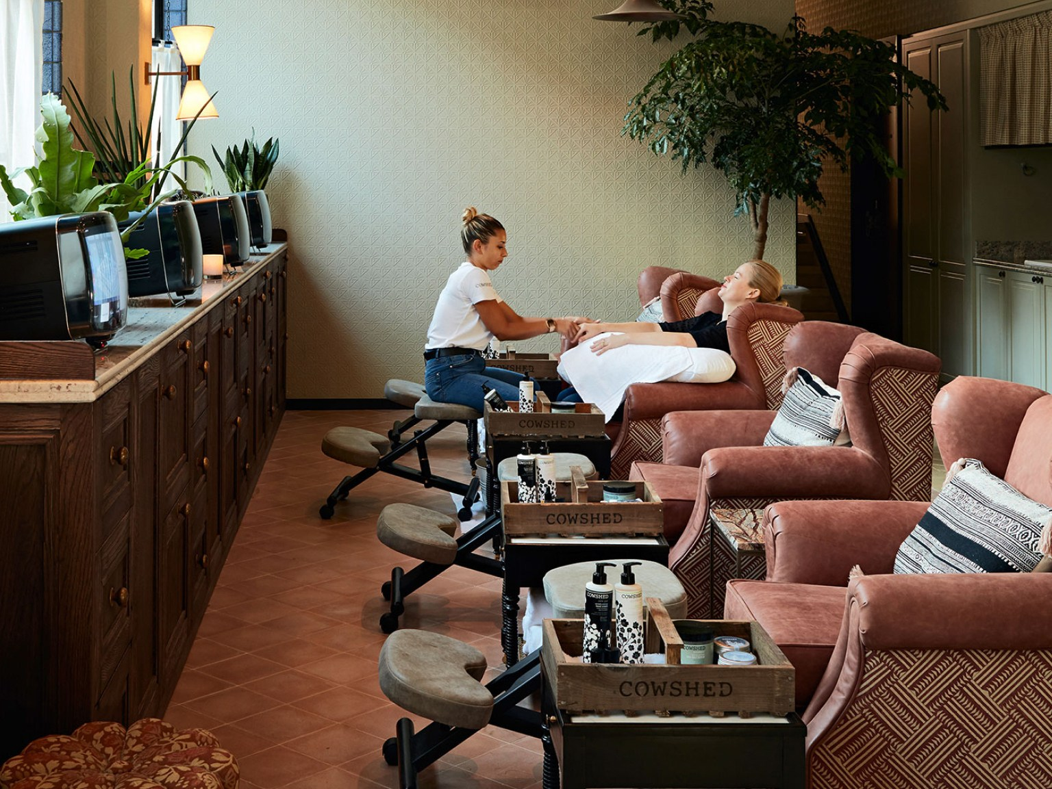 A woman gives another woman a hand massage in a spa.