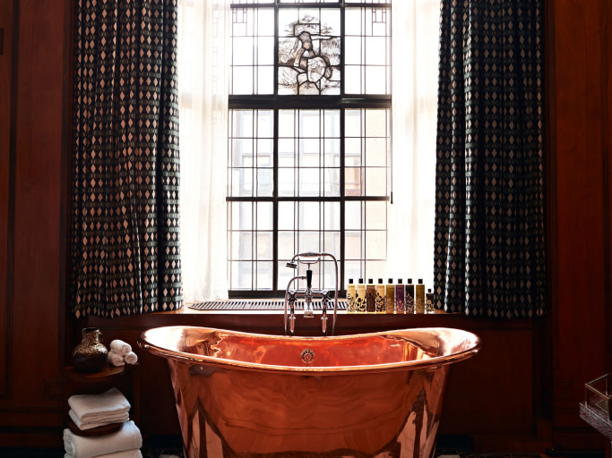 A copper bathtub next to a stained glass window.