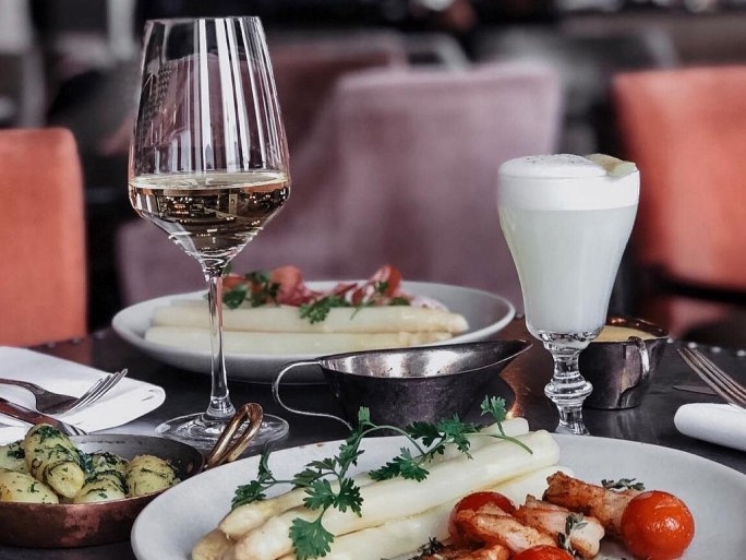 Wine glasses and food on a dining table.