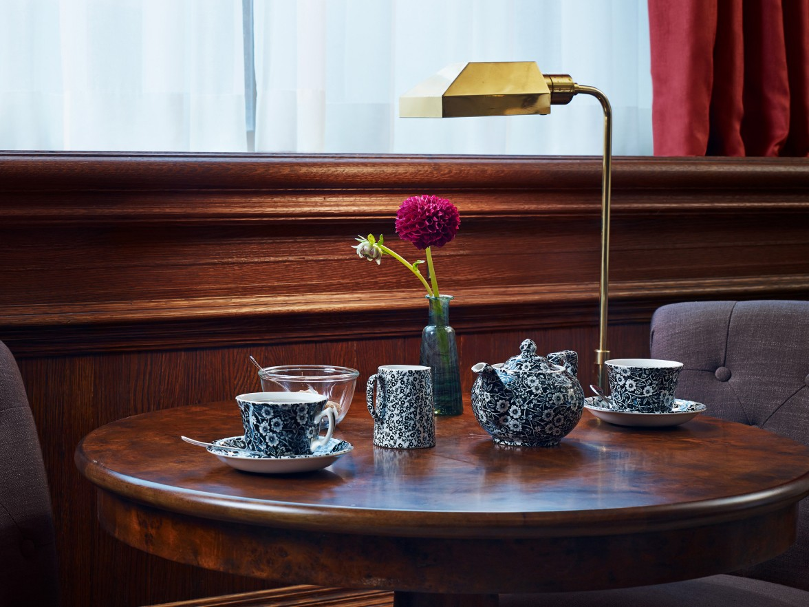 A tea set and lamp on a wooden table.