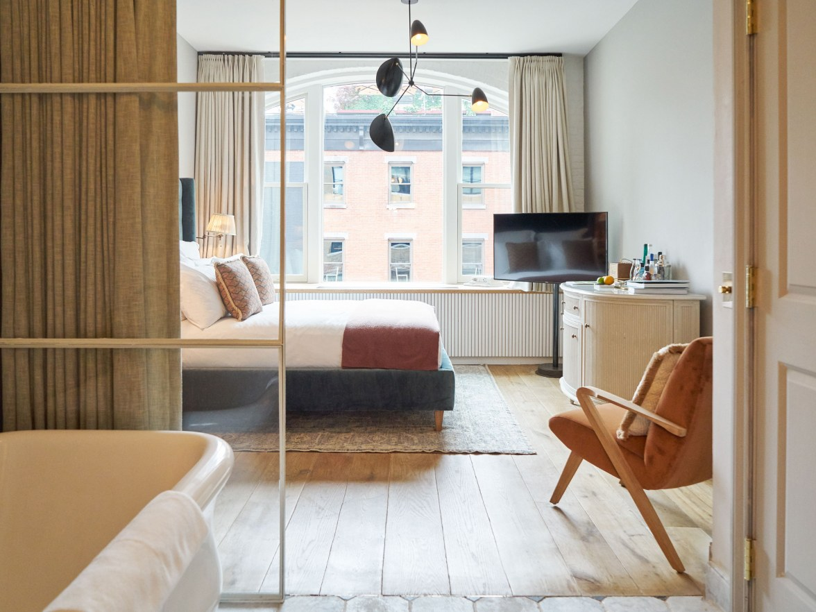 A bedroom with various furnishings looking out onto a city street.