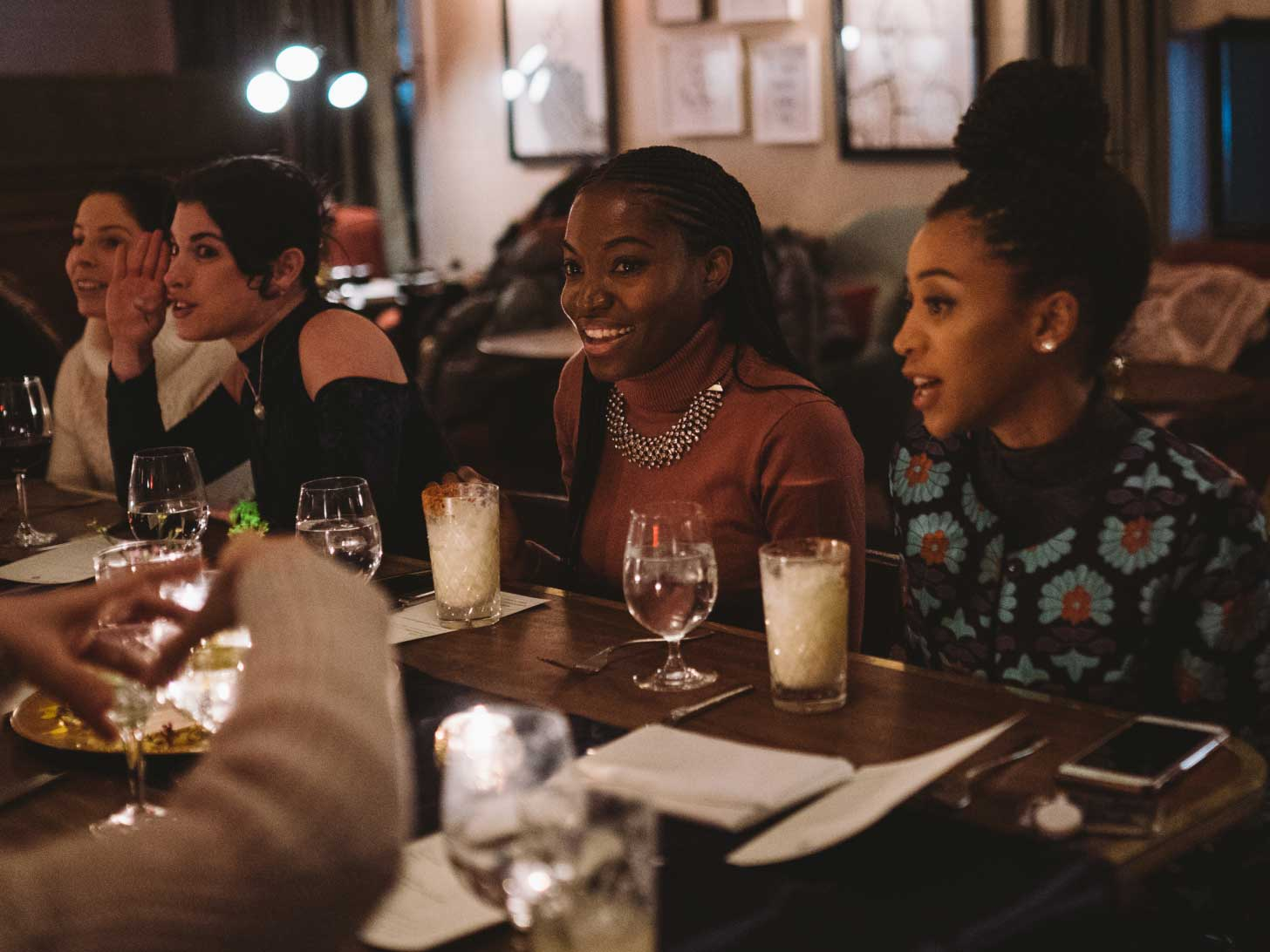 Two women chatting with other people over a formal dinner.