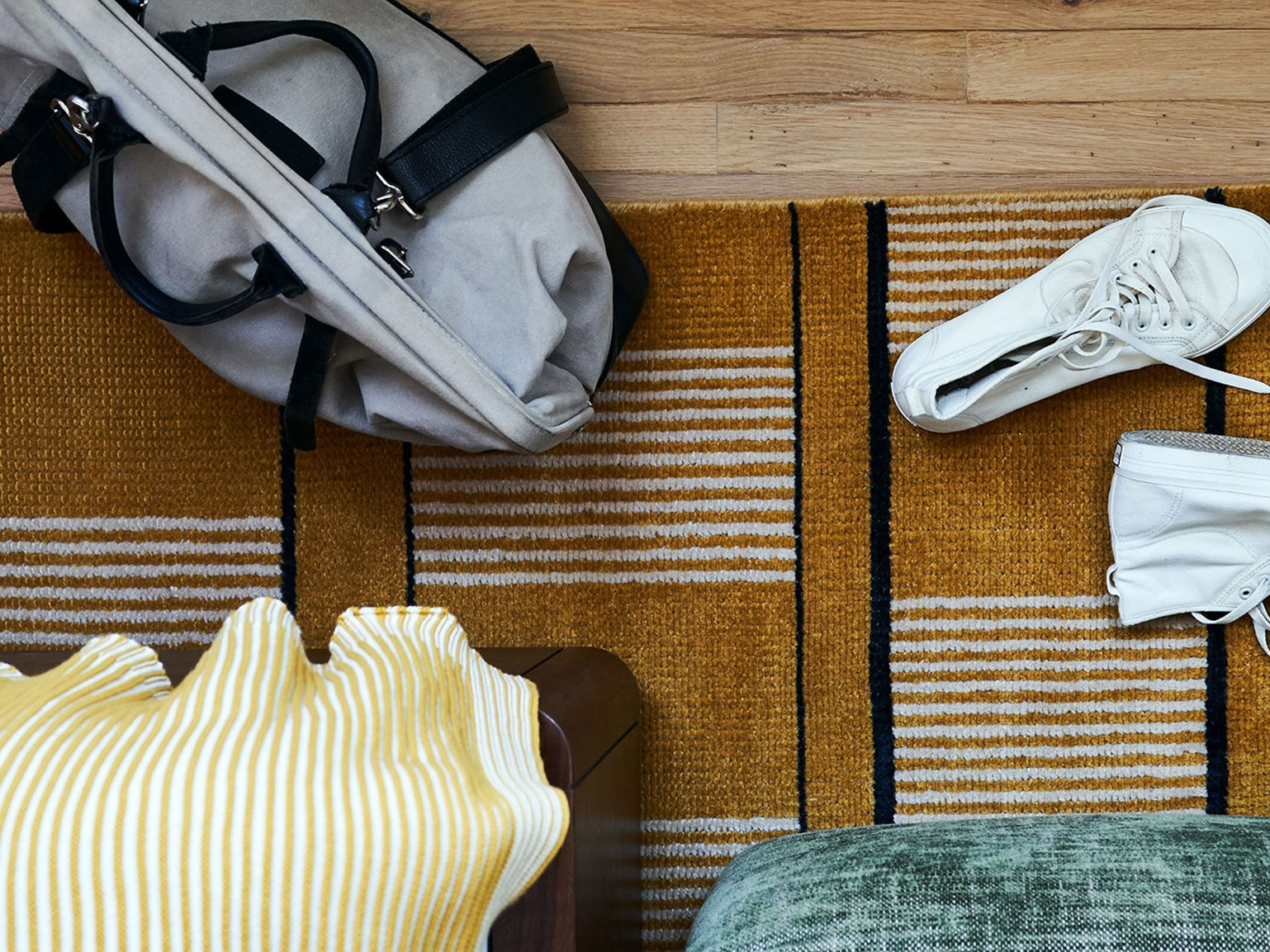 An overnight bag and pair of trainers on a bedroom floor.