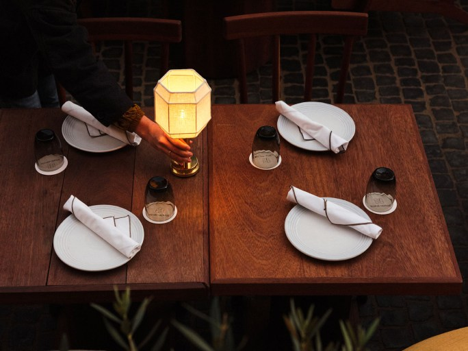 A waitress turning a lamp on a table laid for dinner.
