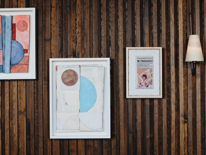Three artworks on a wooden wall.