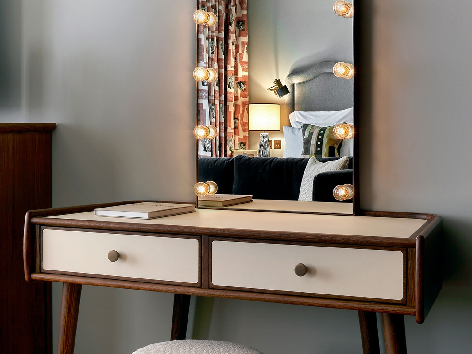 A dresser with a mirror that has lightbulbs going around it.