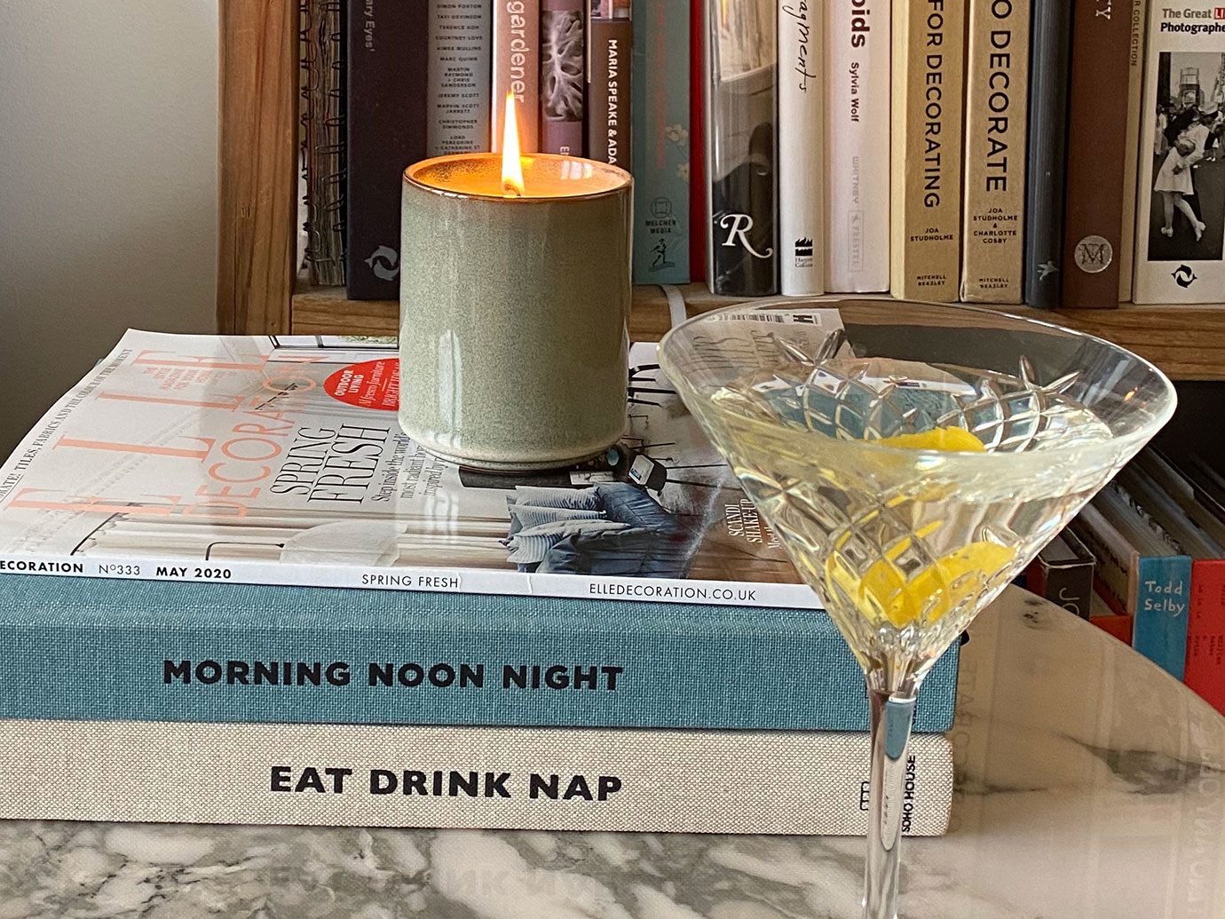 Two books on a table next to a cocktail and a lit candle.