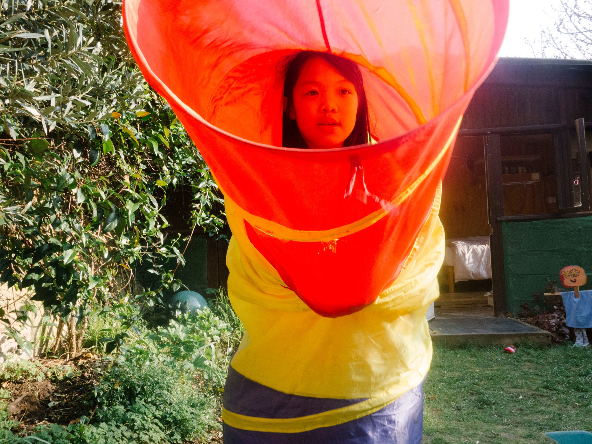 A young girl standing up in a colourful tube in a garden.