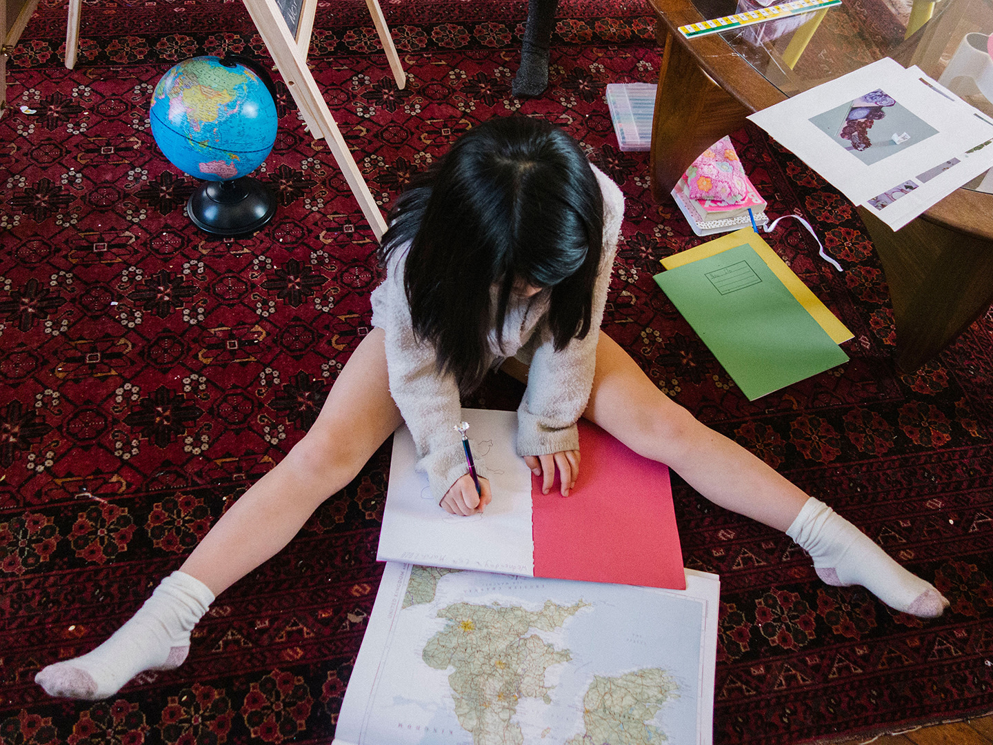 a young girl sitting on the floor with homework and a map