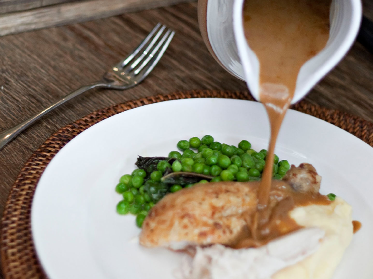 Brown gravy being poured onto a roast chicken lunch.